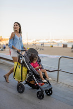 Mother Walking At Beach Promenade With Her Daughter, Sitting In Pram