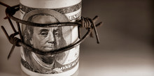 100 US Dollar Bills Wrapped With Barbed Wire As Symbol Of Economic Warfare, Sanctions And Embargo Busting