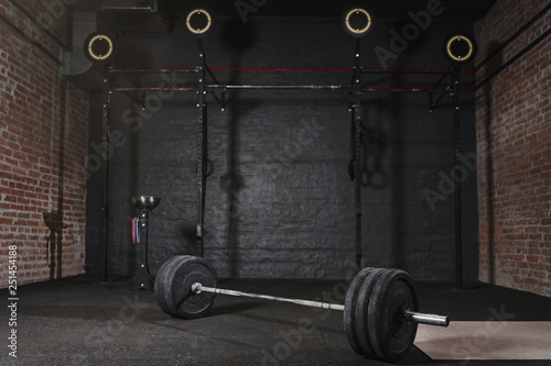 Poster Fitness Crossfit athlete lifting barbell overhead at the gym. Shirtless man doing functional training. Practicing powerlifting.