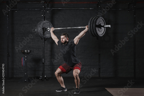 Fotografie, Obraz  Young crossfit athlete lifting barbell overhead at the gym