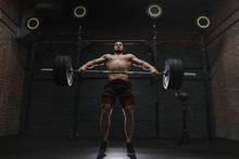 Young Crossfit Athlete Lifting Heavy Barbell At The Gym. Practicing Powerlifting.