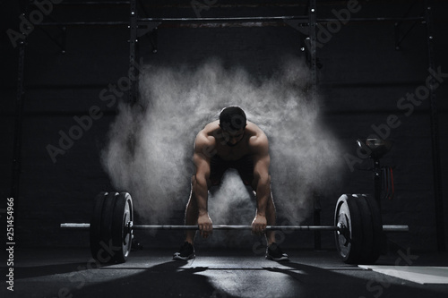Crossfit athlete preparing to lift heavy barbell in a cloud of dust at the gym Wallpaper Mural