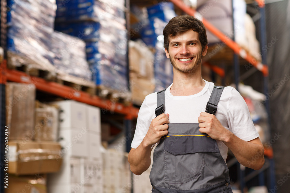 Fototapeta Good looking loader of warehouse posing, smiling and looking at camera. Cheerful worker standing and holding uniform by hands. Forklift and shelves with goods on background.