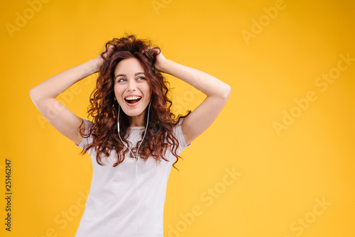 Fototapeta Attractive brunette girl with curly hair isolated over yellow background having fun, listening to music, singing and dancing with earpods on. Music app and online karaoke concept obraz na płótnie