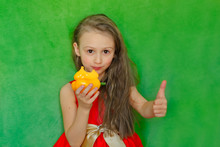 Happy Little Girl In A Red Dress Looks Into The Frame And Eats Yellow Sweet Pepper On A Green Background.Girl Shows Like. Girl With Long Hair Eats Yellow Sweet Pepper On A Green Background