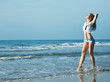 young pretty blond woman at seacoast walking relaxing, fashion lady at sunset