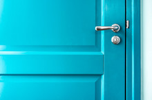 Closed Solid Wooden Door Is Painted In Bright Blue With A Beautiful Metal Handle And Lock.