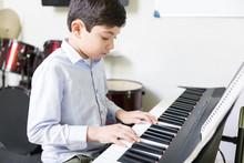 Disciplined Boy Practicing In Piano Class