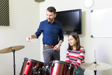 Girl Learning Drumming Lessons In Music Class