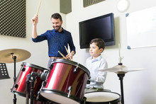 Tutor Giving Drum Lessons To Caucasian Boy