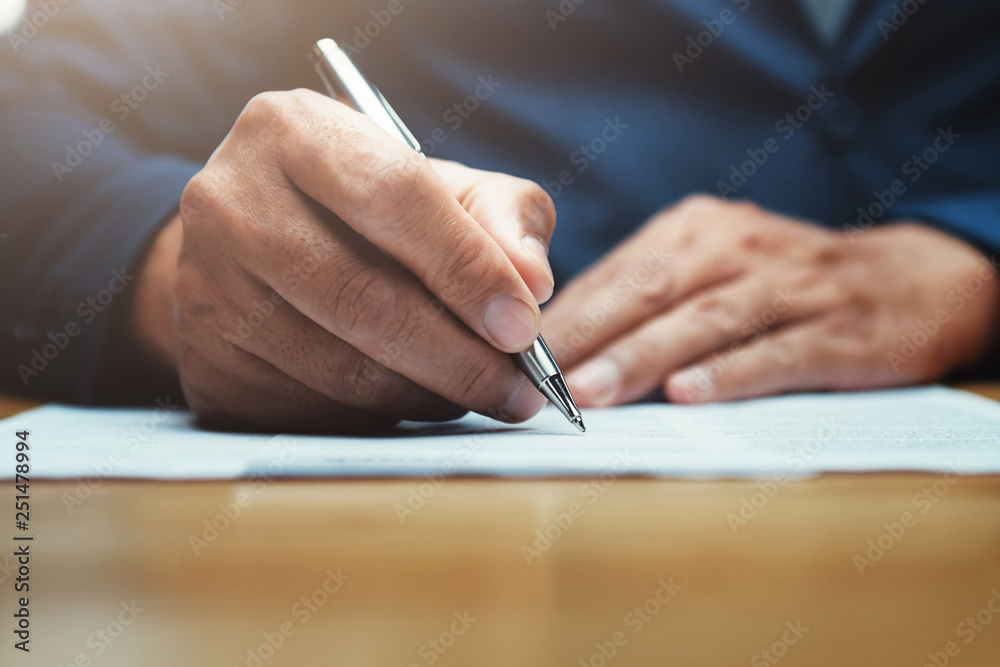 Fototapeta businessman writing on paper report in office
