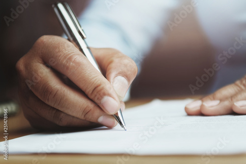 Fotografía hand of woman holding pen with writing on paper report in office