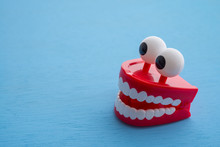 Chattering Teeth Toy Wind Up Moving On Blue Background. Funny, Comedy, Relax Time Concept