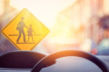School Zone Warning Sign And Inside Car View ,steering Wheel On Blur Traffic Road With Colorful Bokeh Light Abstract Background.