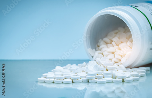 Photo  White tablets pill spilled out from white plastic bottle container