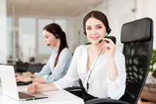 Friendly Young Female Technical Support Dispatcher With A Headset Working In A Call Center On A Hotline, Talking On The Phone. Portrait Of An Attractive Customer Care Representative. Business Concept