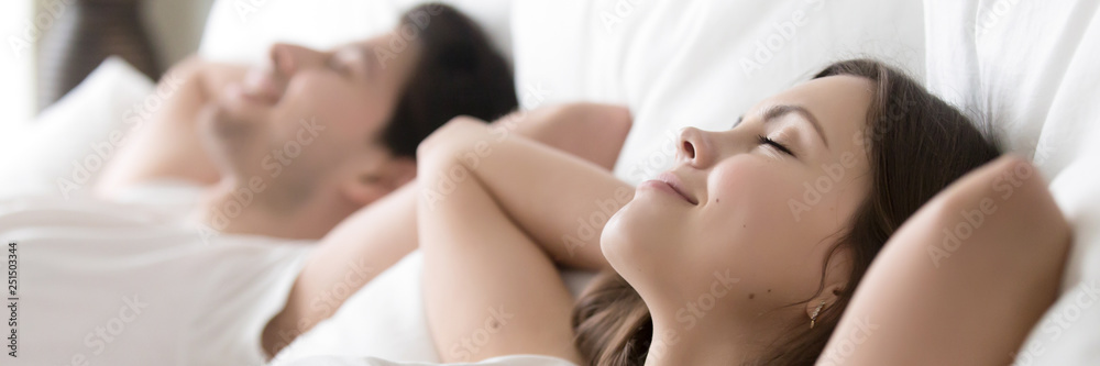 Fototapety, obrazy: Satisfied couple sleeping in bed close up focus on female
