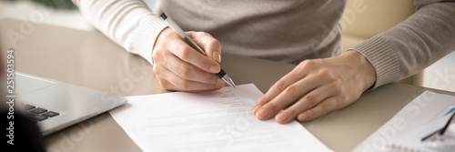 Close up female sitting at table holding pen signing contract Wallpaper Mural