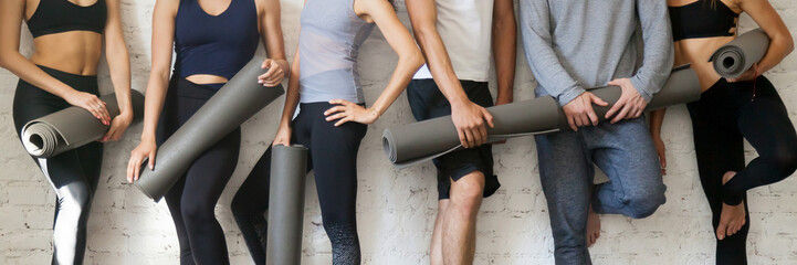 Group people wearing activewear holding yoga mats standing near wall