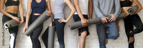 Keuken foto achterwand Fitness Group people wearing activewear holding yoga mats standing near wall