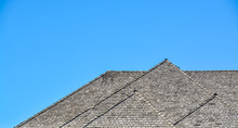 Massive Roofs Of Residential House On Blue Sky Background. Family House With Big Roofs Tiled By Wooden Shingles