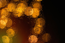 Bokeh Night City Lights Behind Wet Glass During Rain. Can Be Used As Wallpaper Or Background
