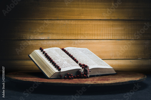 Bible and the crucifix beads on a old round table. Beautiful yellow wooden background. Religion concept.