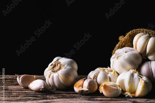 Fototapeta Closeup garlic on wooden texture on for cooking on dark background. obraz