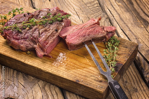 Fotografie, Obraz  Juicy medium rare beef steak slices on wooden  board with herbs spices and salt