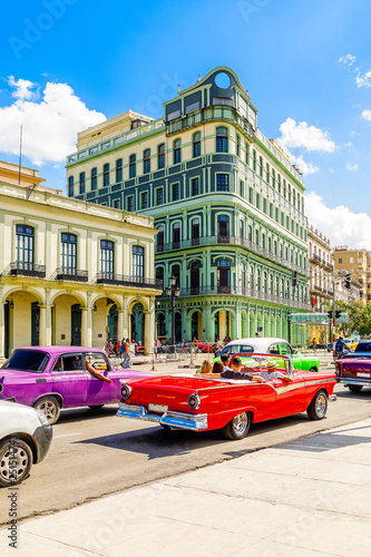 Old colonial buildings across the road with driving retro red ca