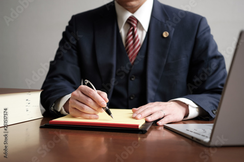 Fototapeta リーガルパッドにメモをする男性弁護士 obraz
