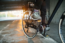 Midsection Of Businessman Commuter With Electric Bicycle Traveling From Work In City.