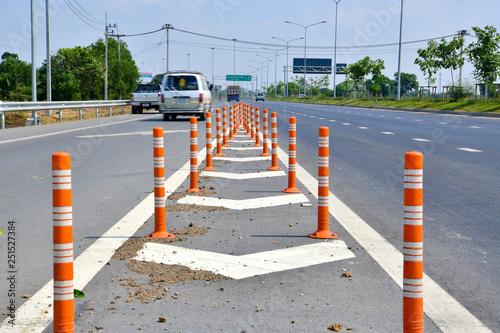 Photo Orange traffic pole or flexible traffic bollard on asphalt road for crossroad