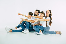 Beautiful Happy Smiling Family In T-shirts Pointing Together Away Isolated On White Background