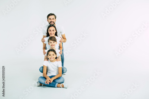 Obraz Happy cute smiling family looking on camera isolated on white studio - fototapety do salonu