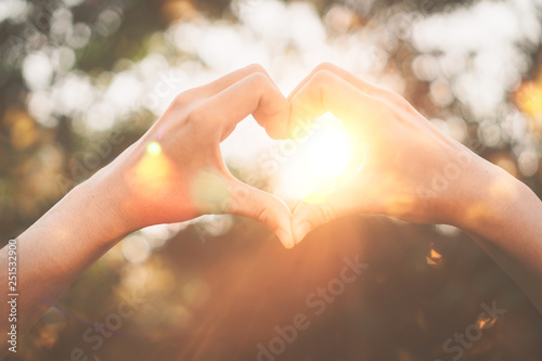 Poster Printemps Female hands heart shape on nature bokeh sun light flare and blur leaf abstract background.