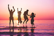 canvas print picture - Happy friends jumping inside water on tropical beach at sunset