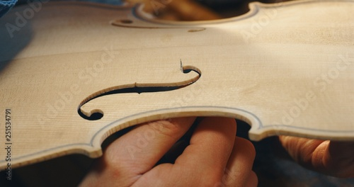 Fotografie, Tablou Macro close up of master artisan luthier painstaking detailed work on wood violin in a workshop