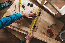 Man Assembly Wooden Furniture,fixing Or Repairing House With Yellow Tape Measures