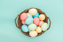 Top View Of Pastel Easter Eggs In Wicker Basket Isolated On Blue