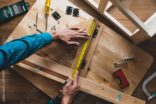Fotografie, Tablou  Man assembly wooden furniture,fixing or repairing house with yellow tape measure