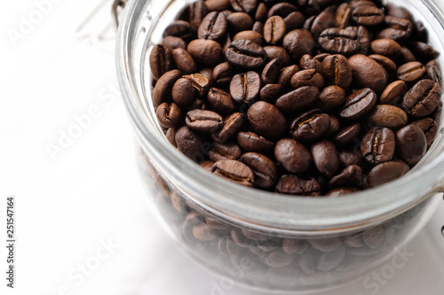 Canvas Prints Coffee beans Close up dark roasted coffee beans in a glass jar on white cotton fabric background in natural light