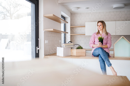 Photo  A young woman moving in new home, sitting on a counter in the kitchen