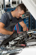View from side of serious mechanic in uniform and protective gloves fixing motor of car in auto service. Professional worker repairing broken vehicle with wrench. Concept of maintenance.