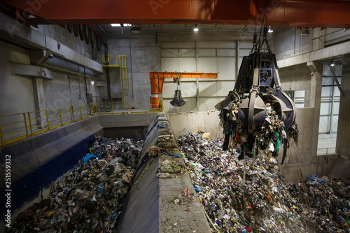 Fototapeta Mechanical claw hand grabbing pile of mixed waste