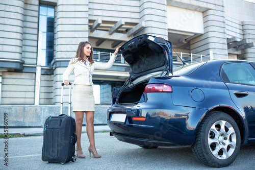 Stampa su Tela Fancy dressed young woman closing the trunk of the vehicle