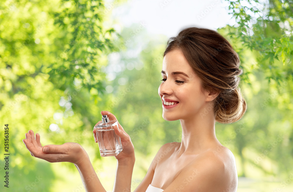 Fototapety, obrazy: perfumery, beauty and luxury concept - happy smiling young woman spraying perfume to her wrist over green natural background