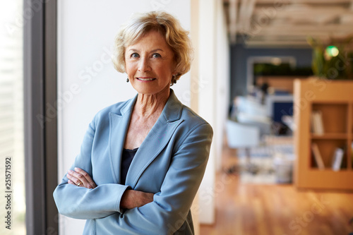 Photographie Portrait Of Smiling Senior Businesswoman In Modern Office Standing By Window