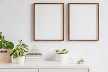 Elegant Home Interior With Two Brown Wooden Mock Up Photo Frames Above The White Shelf With Books, Plants, Gold Pyramid, Wooden Box And Home Accessories. Stylish Concept Of White Room Decor.