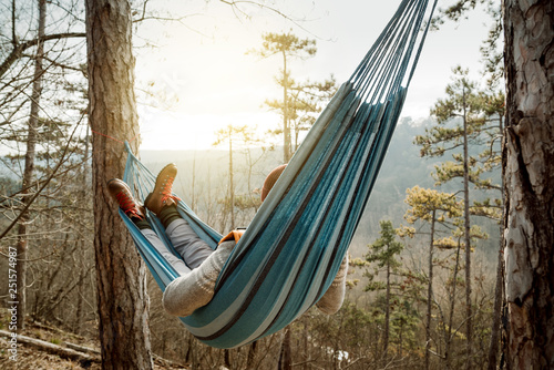 Poster Relaxation Young happy man relaxing lying in hammock on top of mountain.